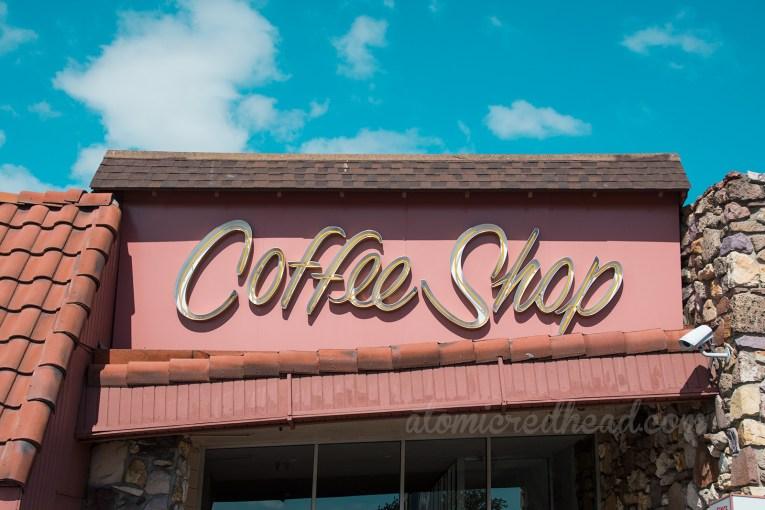"Above the door in yellow neon reads ""Coffee Shop"""