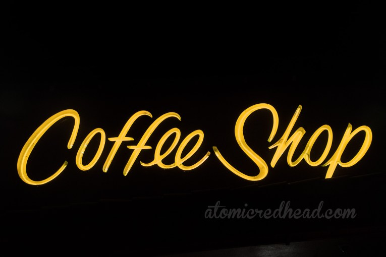 "Above the door in yellow neon reads ""Coffee Shop"""