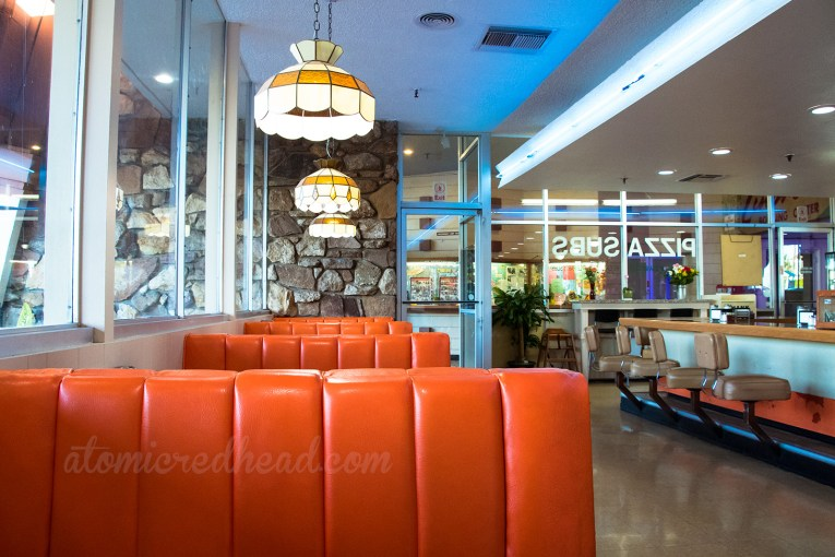 Inside the coffee shop, orange vinyl booths, with a rock wall along the back.