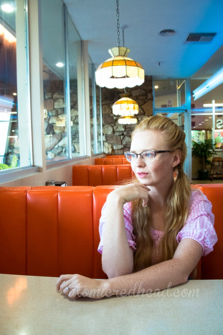 Me, seated at one of the booths, looking out the window, wearing a white and pink gingham top.