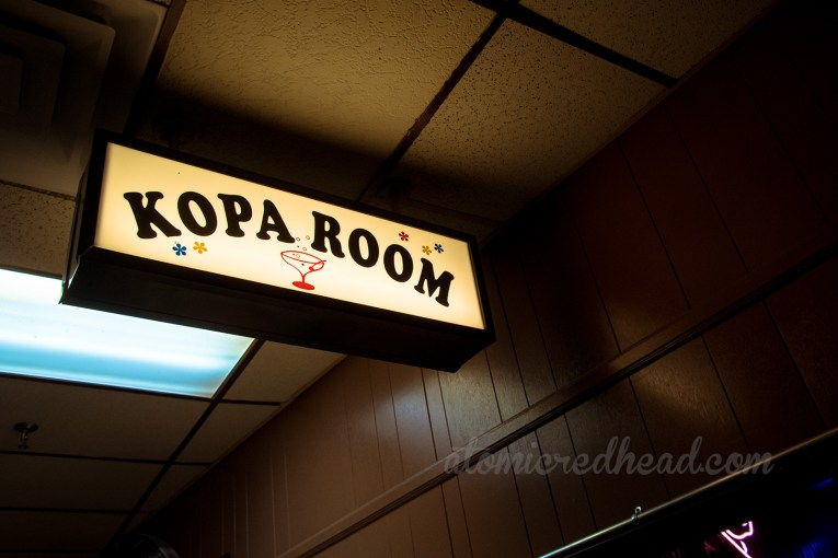 The sign for the Kopa Room, white, with blue bubbles and a pink cocktail