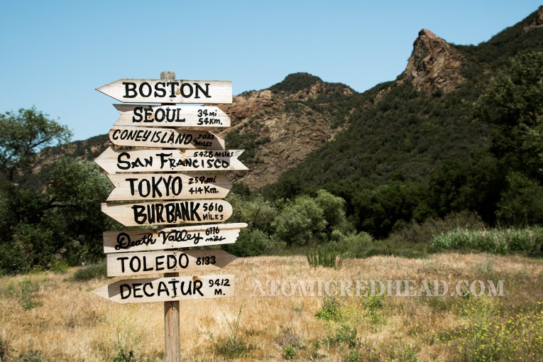 The notable sign post, reading where places, including where some characters were from, and how far to those places - Boston, Seoul, Coney Island, San Francisco, Tokyo, Burbank, Death Valley, Toledo, Decatur