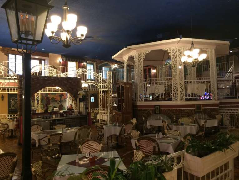 Interior of the French Market Place. A tall ceiling painted midnight blue evokes a feeling of being outside, with exposed brick and wrought iron gazebo centered. Image from Yelo.