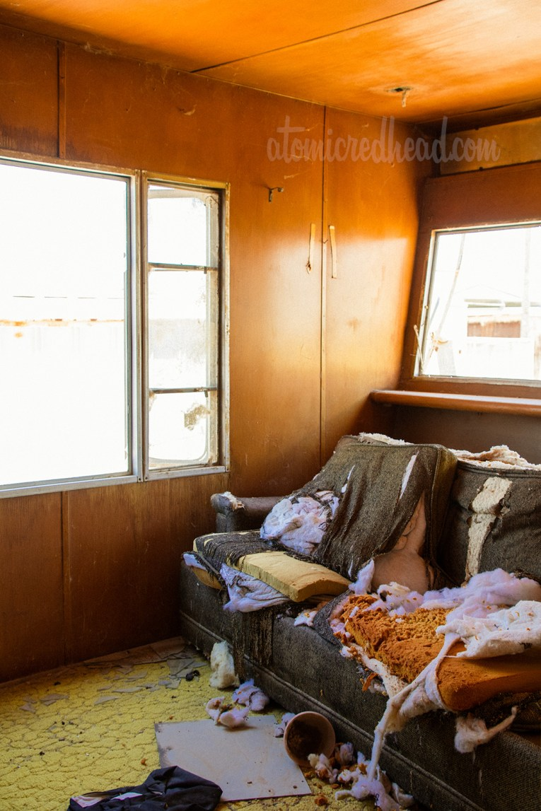 Inside abandoned trailer, with a couch that has been slashed open and trash scattered about