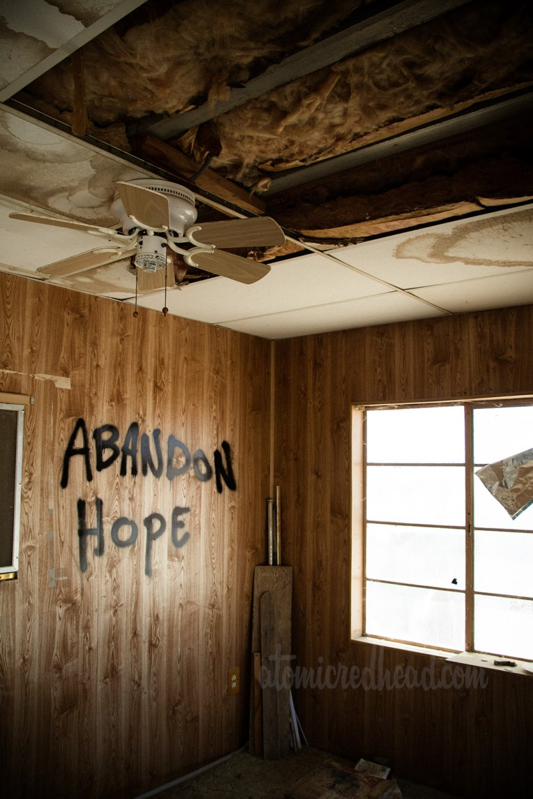 "Inside a trailer, with a broken drop down ceiling, faux wood paneling, and has been tagged with ""Abandon Hope"""