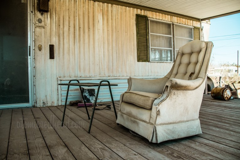 A white upholstered chair sits upon the porch of a trailer, tattered and dirty.