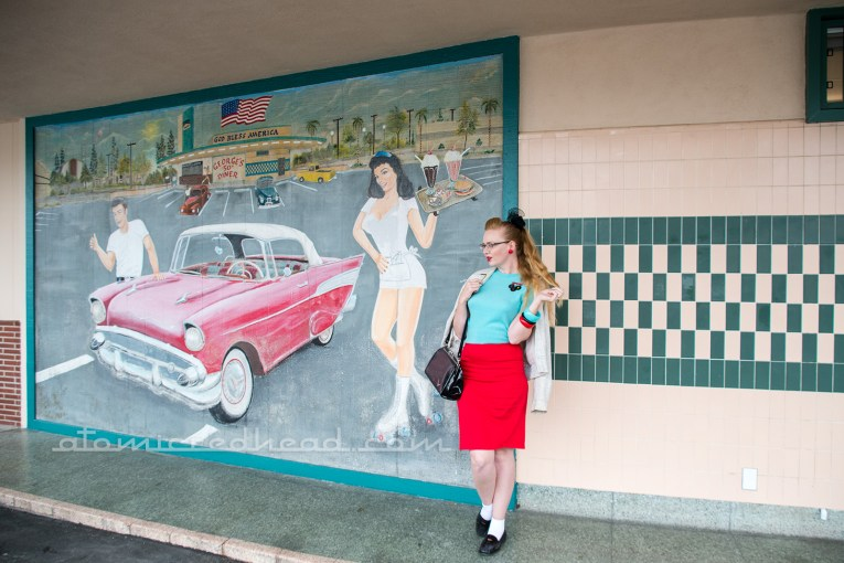 Me, standing outside of George's 50s Diner, wearing a vintage white Ricky jacket, turquoise sweater, red pencil skirt, and black penny loafers.