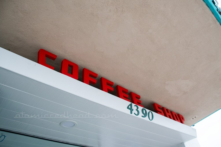"Red letters spell out ""Coffee Shop"" outside"