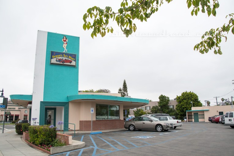Exterior of George's 50s Diner, a flat roofed building, with rounded corners, and a large rectangle jutting from the top for signage. The building is painted in cream and turquoise.