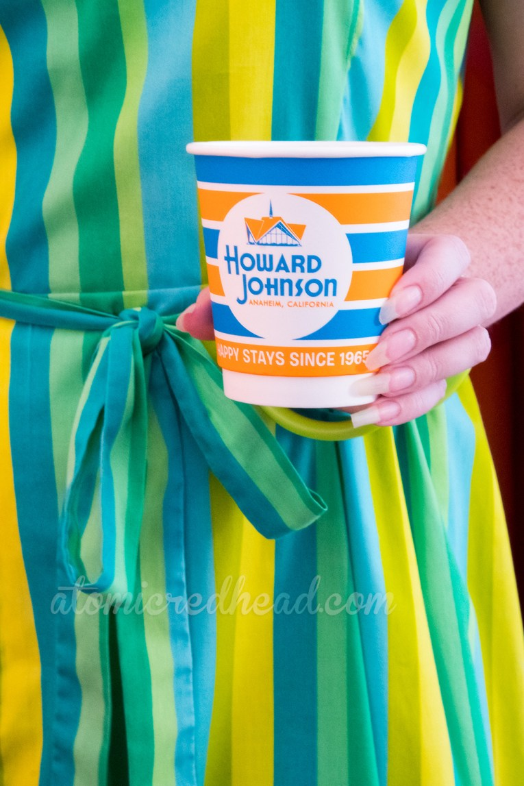 "One of the retro HoJo cups, orange and turquoise stripes and a circular logo reading ""Howard Johnson Anaheim, Happy Since 1965"""