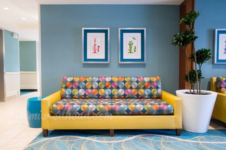The hallway lobby of one of the towers, featuring geometric patterned carpet, blue walls, and a yellow and multi-colored geometric patterned couch.