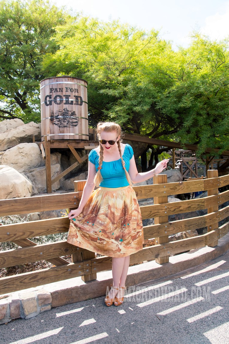 Me, wearing a teal blue peasant top, and a border print skirt of miners panning for gold.