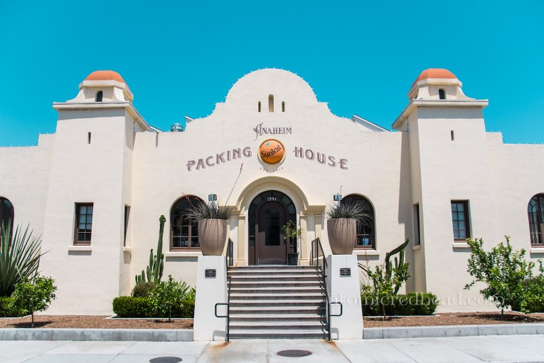 """The Packing House, a mission revival styling building with cream colored stucco and orange color domes. A large orange with """"Sunkist"""" across it pops just slightly from the middle above the door."""