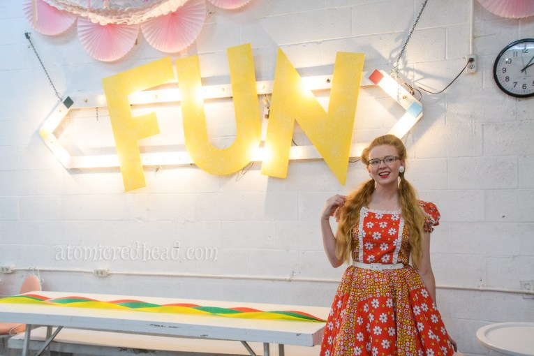 "Standing inside the party room where ""FUN"" is spelled out in large yellow letters."