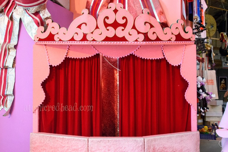 One of the traveling theaters, pink felt swirls around a red curtain.