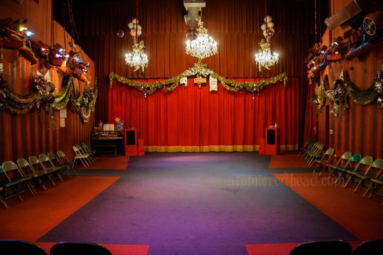 The theater inside - red velvet curtains hang all round, three chandeliers hang, gold garlands trim the edge.