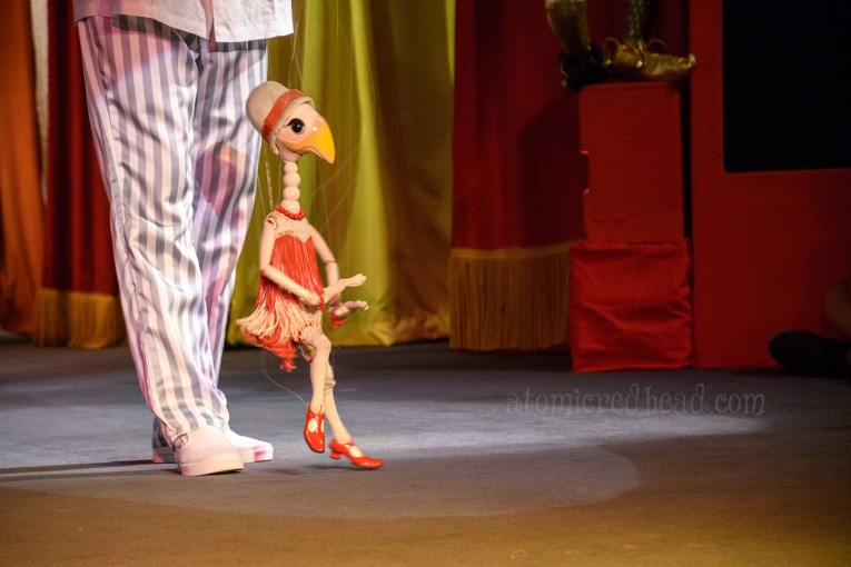 A fanciful goose marionette dressed like a flapper in a ride and white fringe outfit.