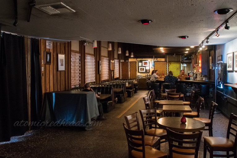 Inside the Kibitz Room, dark wood paneling, and black vinyl booths line the walls.