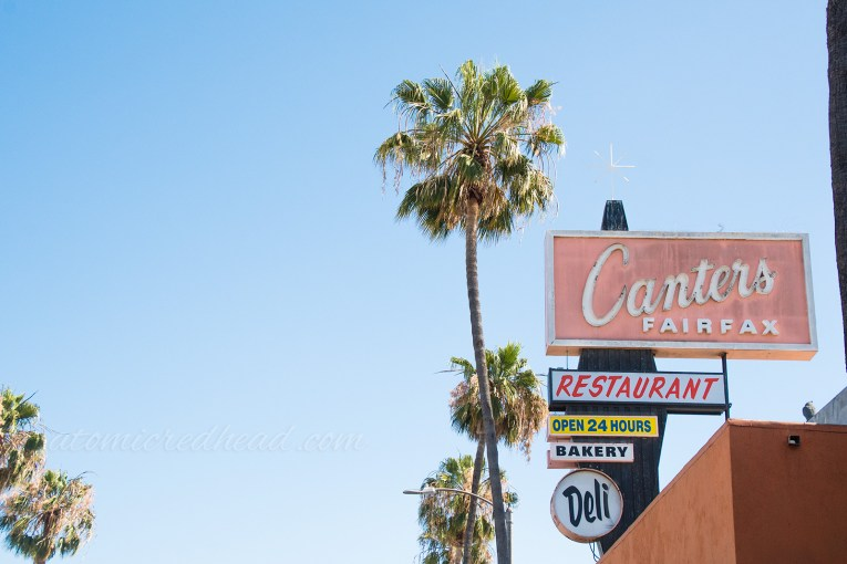 "The large sign on Canter's rooftop, a black diamond shape extends upwards with a large red rectangle reading ""Canter's"" a circular sign below reads ""Deli"""
