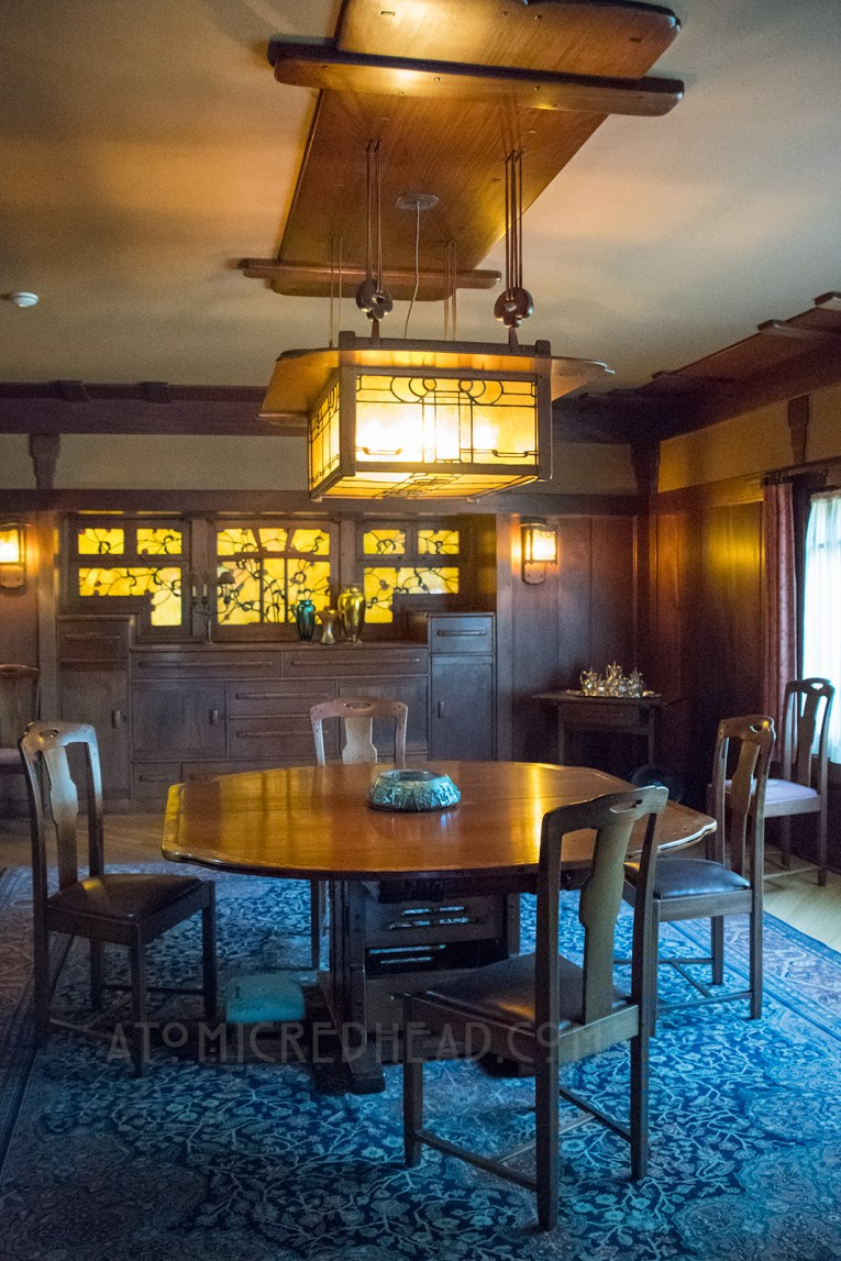 The dining room, dark wood walls, with stained glass of leaves in the back.