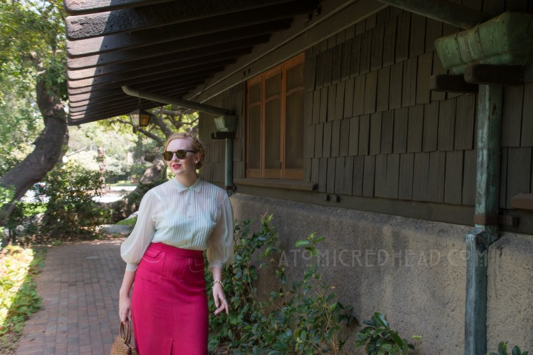 Standing near the garage of the Gamble House, wearing a pale blue sheer blouse and magenta skirt with white trim, and a brown woven basket purse.