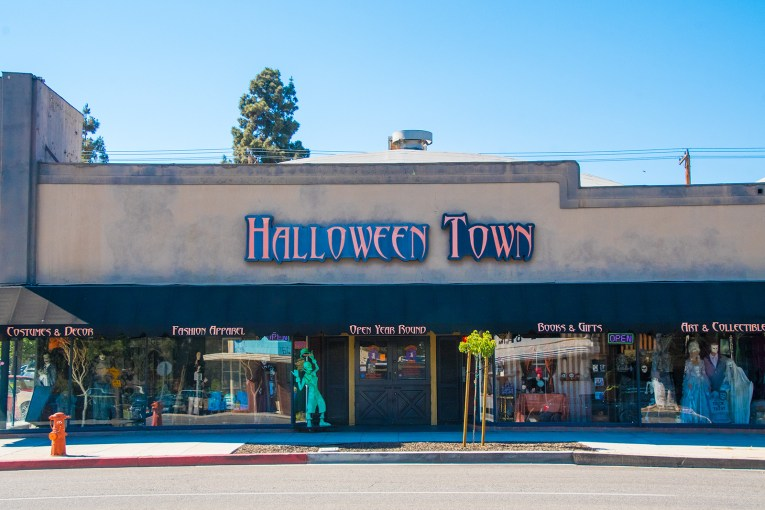 "Storefront for Halloween Town. Large creepy text reads ""Halloween Town"" in orange and black letters, windows are filled with tombstones, vampires, goblins, and fortune tellers."