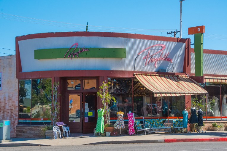 """Storefront of Playclothes, featuring vintage clothing and furnishings outside. A green and pink sign outside reads """"Playclothes"""""""