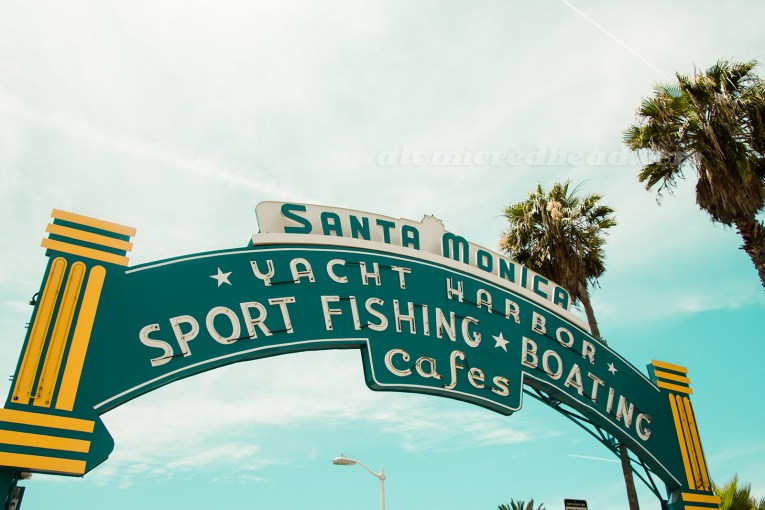 """Neon arch above the pier, reading """"Santa Monica Yachy Harbor, Sport Fishing, Boating, Cafes"""""""
