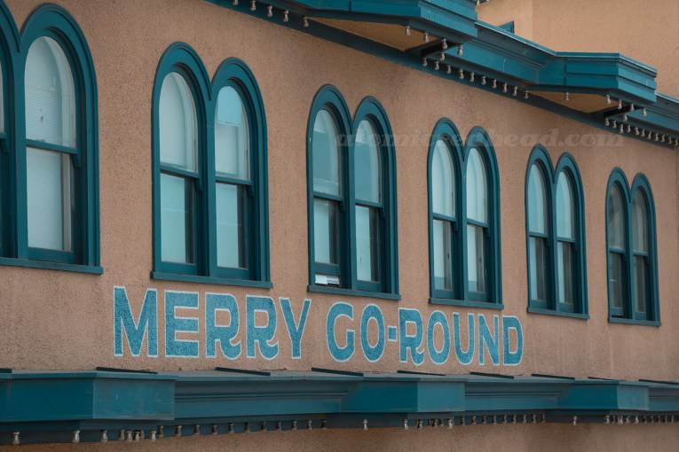 """Side of the Hippodrome, a tan building, with navy blue trim, and painted on the side """"Merry-Go-Round"""""""