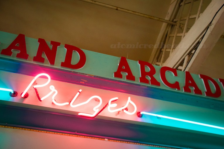 """Inside Playland, pink neon reading """"Prizes"""""""