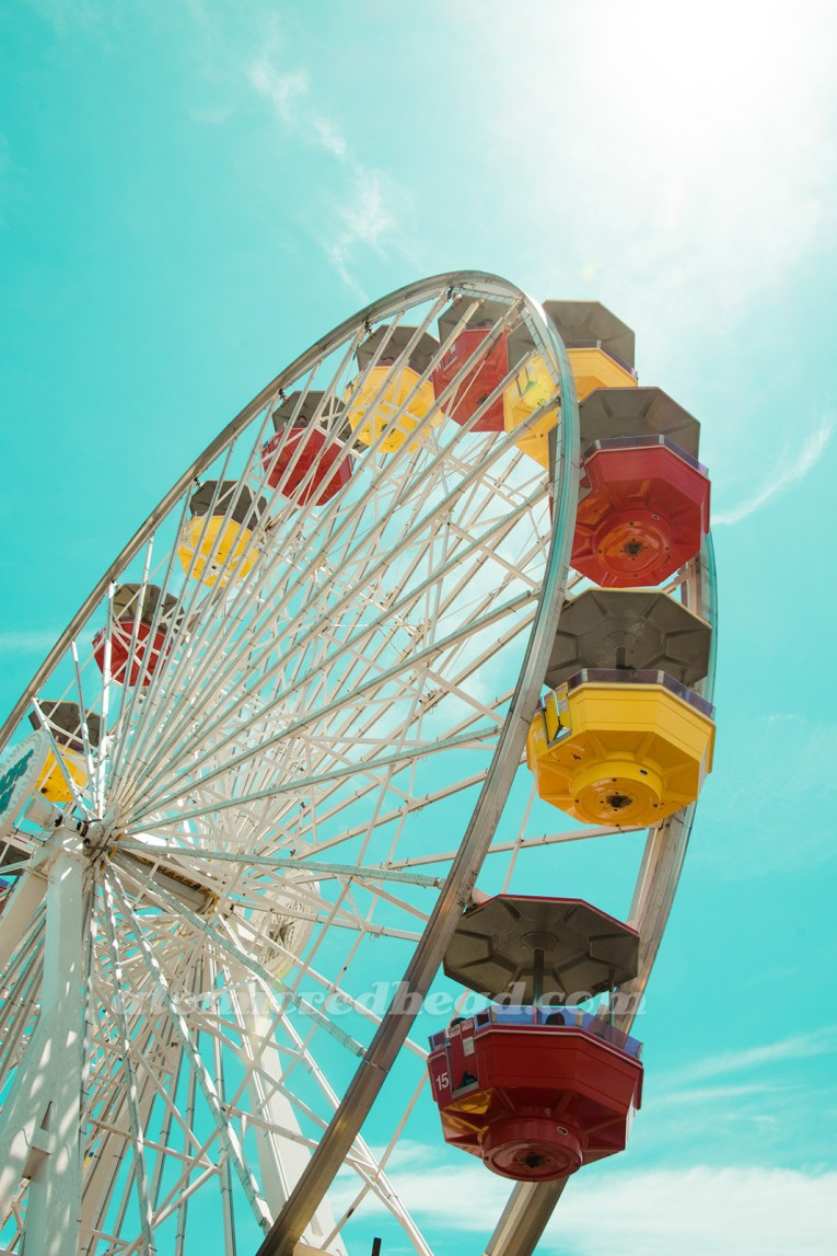 The ferris wheel at Pacific Park, with baskets of red and yellow.