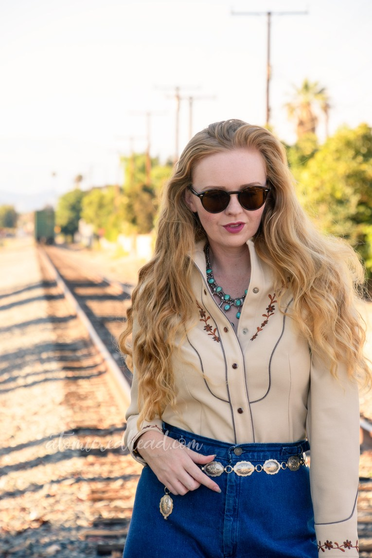 Me wearing a 70s western wear shirt, tan with small embroidered flowers, a turquoise squash blossom, and wide leg 70s jeans, standing along railroad tracks.