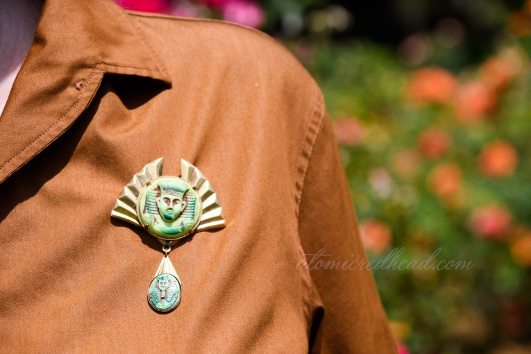 A close up of my brooch, gold metal with a green glass image of King Tut.