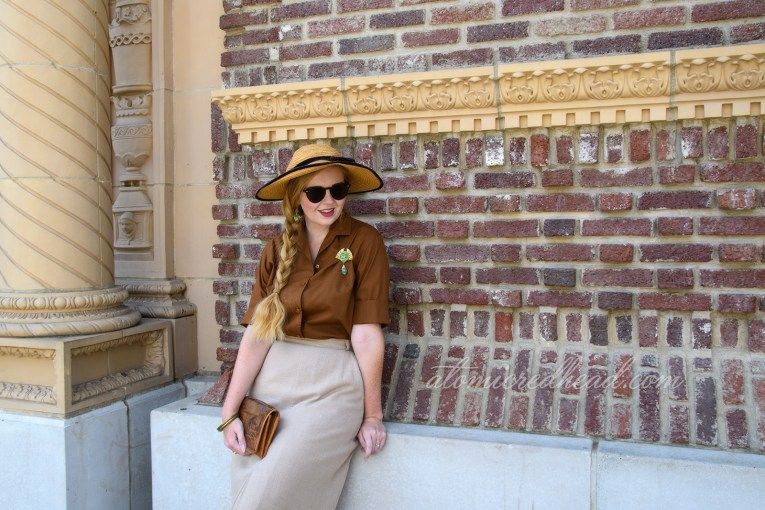 Me, standing against a brick wall, wearing a brown blouse and tan skirt, and wide bring straw hat with brown velvet trim