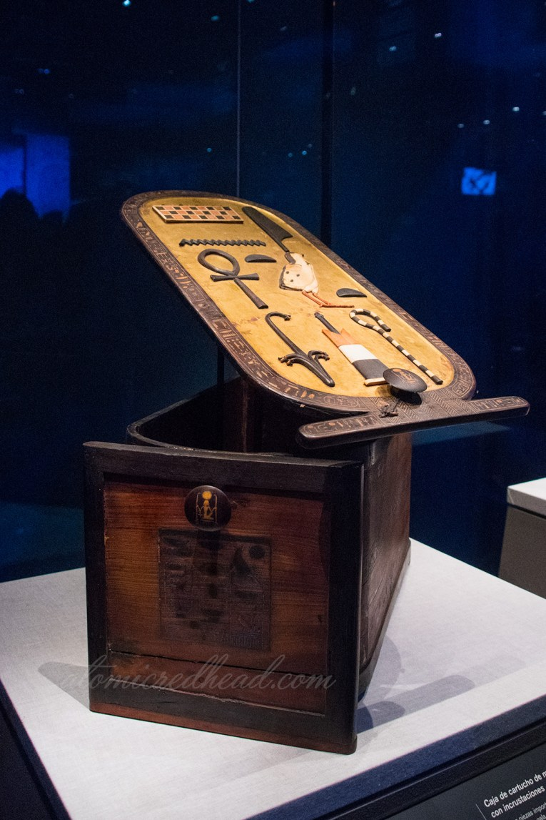 A carved box where the lid is a cartouche featuring Tut's name.
