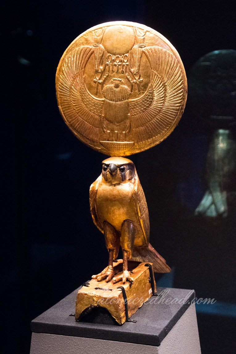 A statue of Horus with a large sun disc above featuring a winged scarab.