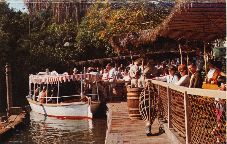 Guests board the boats of the Jungle Cruise, white boats with red and white stripe canopies.