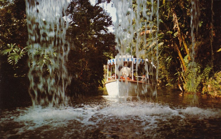 A Jungle Cruise boat glides by Schweitzer Falls.