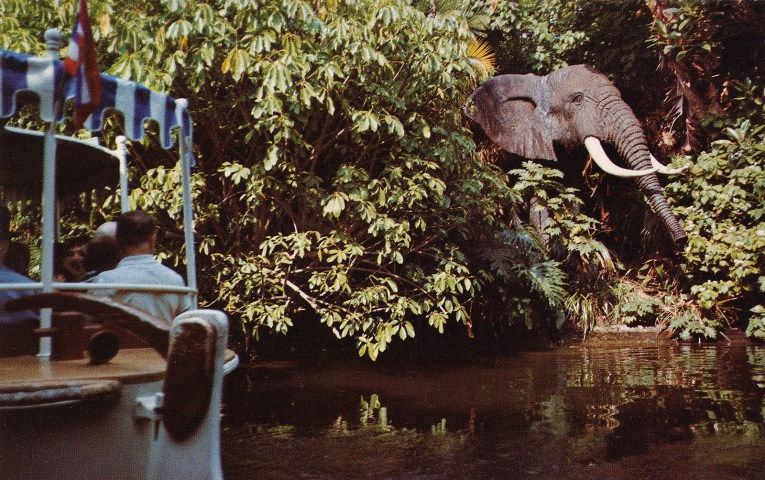 A Jungle Cruise boat glides by a large African Bull Elephant.