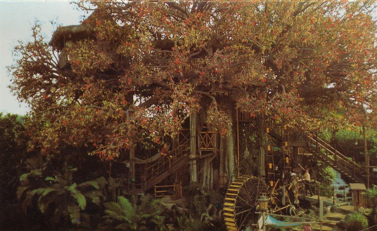 The Swiss Family Robinson Treehouse, a large faux tree with tan colored leaves. A waterwheel made of bamboo turns on the right, and stairs made of wood, bamboo, and rope allow guests to climb up.