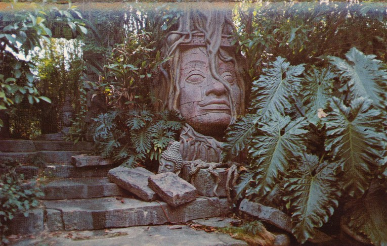 The ruins of a temple, including a massive stone face with vibes growing over it sit along the banks of the Jungle Cruise.
