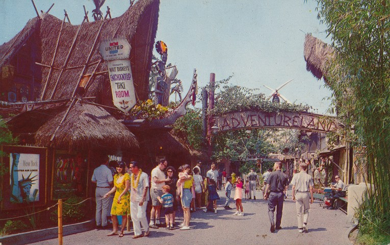"The entrance to Adventureland, a combination of tiki and African culture merge together. Crossed elephant tusks stand above the text reading ""Adventureland"" that is spelled out in wood. The Enchanted Tiki Room off to the left."