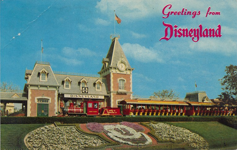 """A look at the Main Street Train Station, with """"Greetings from Disneyland"""" across it. A floral version of Mickey greets guests."""