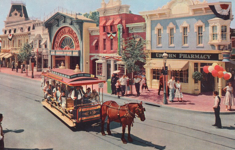 The Horse-Drawn Streetcar goes down Main Street. Pastel Victorian buildings stand tall in the background.