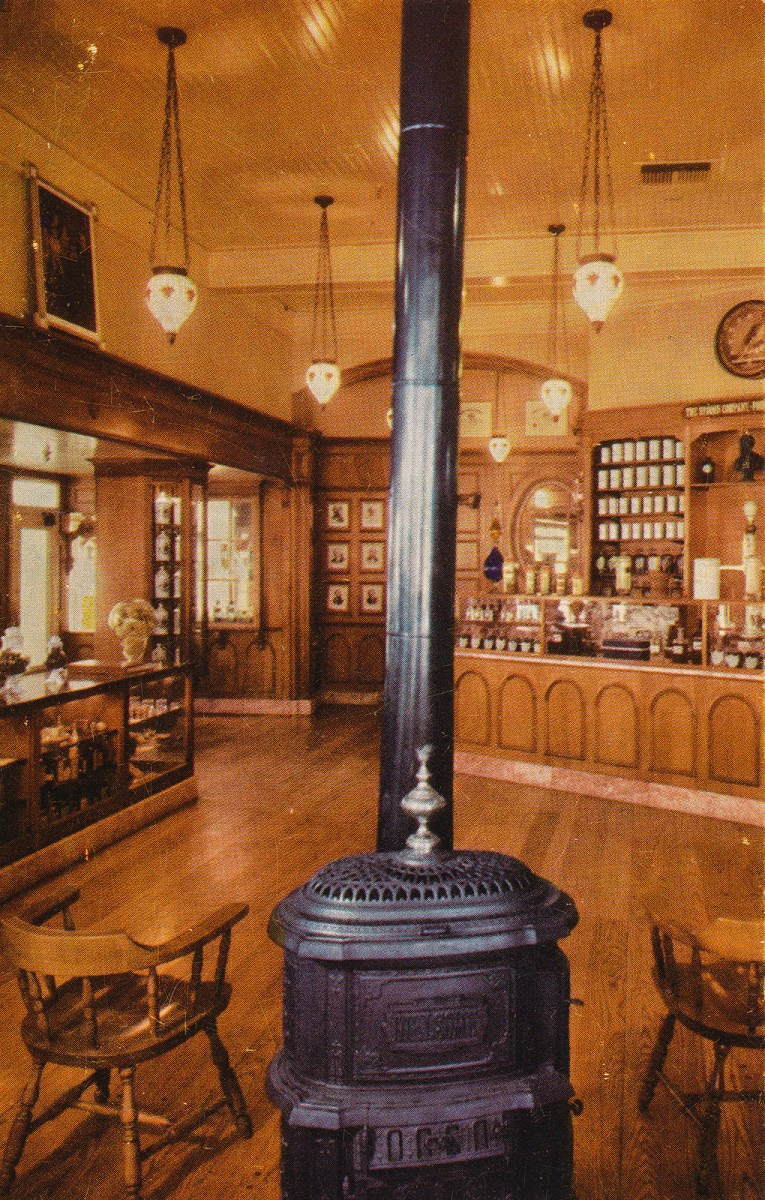 Inside the pharmacy, with a potbelly stove and warm wood walls and old bottles lining the walls.