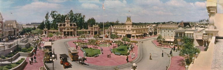 Large panoramic of Disneyland's Main Street, sweeping from the train station on the left, followed by City Hall, then the Emporium, and the Wurlitzer shop on the left.