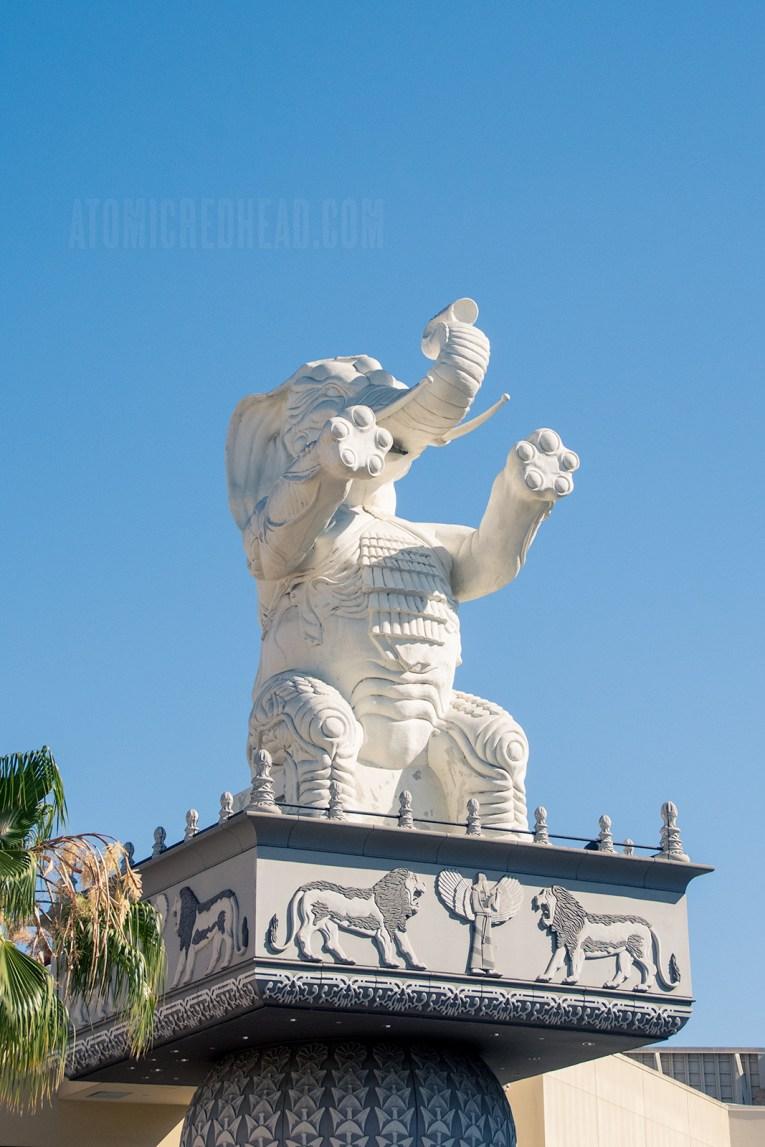 A giant white elephant sits atop a tall pillar.