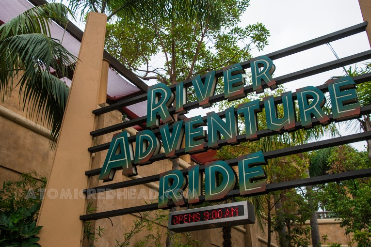"""After passing through the archway you pass under the sign reading """"River Adventure Ride"""" in green text."""