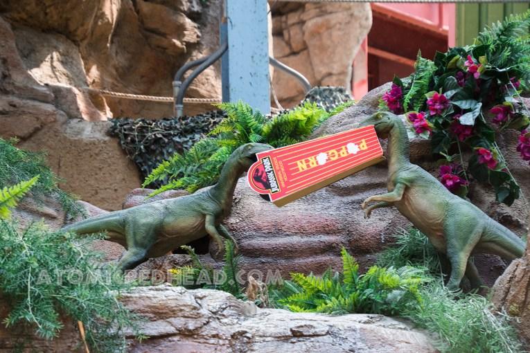 Tiny dinos fight over a box of popcorn.