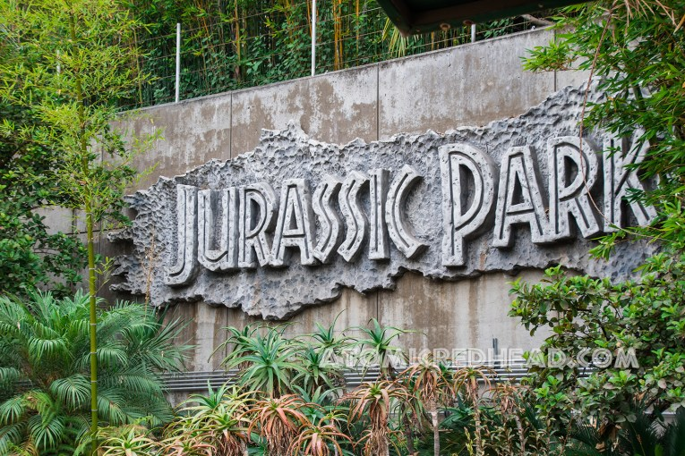 """In large rock work text reads """"Jurassic Park"""""""